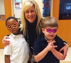 A Staff Member hugging two Students wearing Paper Glasses