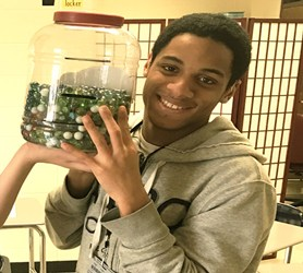 Student holding a large jar half full of many round balls