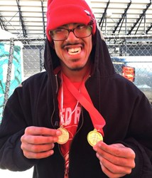 A Student holding two Special Olympic Metals