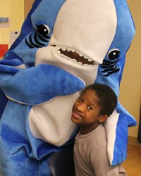 A person dressed up in a Shark Outfit hugging a Student
