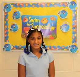 Girl Standing in front of a sign that says Swimming for Success