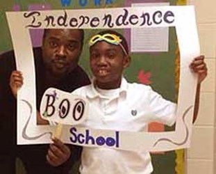 A Student holding a white frame that says Interdependence School