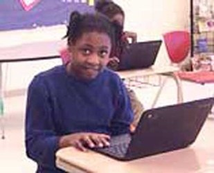 A Student sitting at a School Desk working on a Laptop Computer